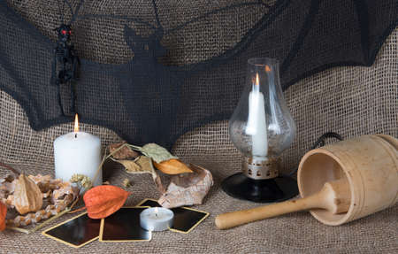 Magic witch ritual. Candles, bat and tarot cards. Mystical atmosphere of fortune telling. Divination still life by candlelight in the evening. Esoteric concept.