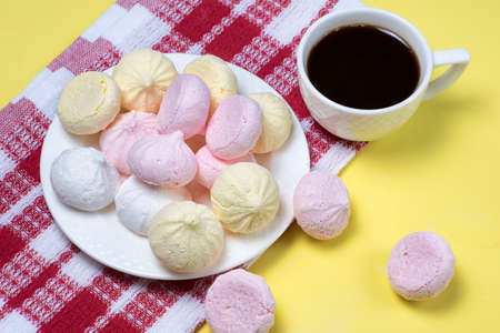 Small homemade meringue kisses. Meringue cookies and coffee cup on red tablecloth and yellow background.