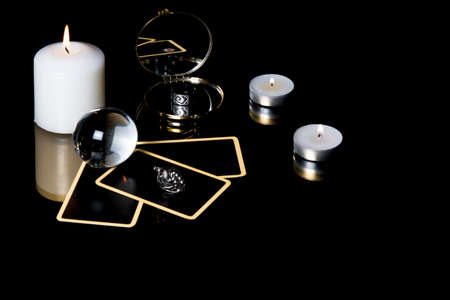 Christmas magical sessions with tarot cards, candle, ring and mirror isolated on black background. Mysterious Christmastide fortune telling. Magic atmosphere.