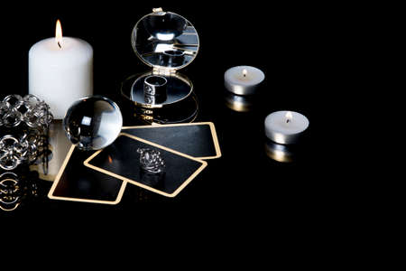 Christmas magical sessions with tarot cards, candle, ring and mirror at night in dark room. Mysterious Christmastide fortune telling. Magic atmosphere.
