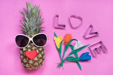 Pineapple with sunglasses, message love, tulip flowers on pink background. Happy women's day concept