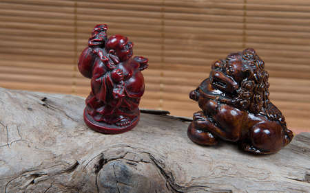 closeup of japanese netsuke figure on wooden and bamboo background. Statue japanese god and lion mascots