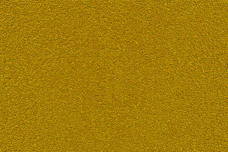 Golden terry towel background. Yellow texture of terry cloth