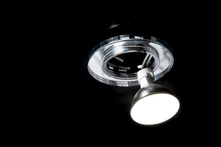 Mounting led ceiling lamp or recessed halogen lights on black suspended ceiling in room, close up.