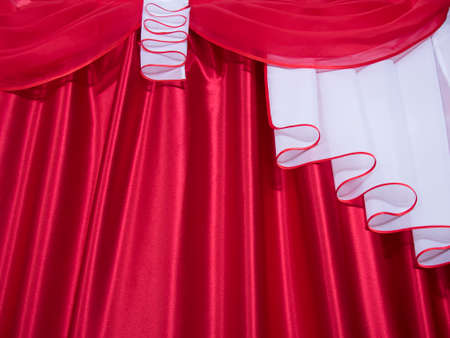Close up of red and white color lambrequin and curtains, silk texture with folds, fabric background
