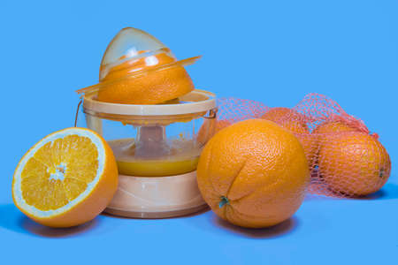 Electric press juicer with cut orange isolated on blue background. Manual juice extractor. Juicing oranges.