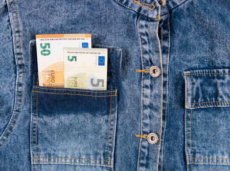 Fifty euro notes in pocket of blue jeans shirt. European union money bills in jeans pocket, closeup. 免版税图像
