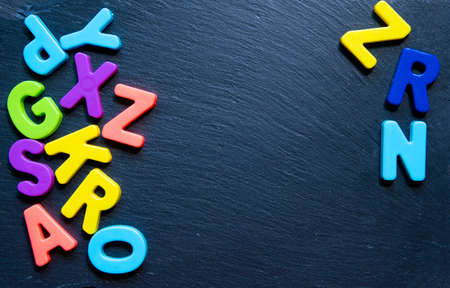 Frame from multicolored letters on black stone background. Topview. Copyspace. Concept back to school.