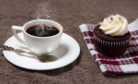 Steaming white coffee cup and homemade cupcake on brown fabric background, homemade cake with cream