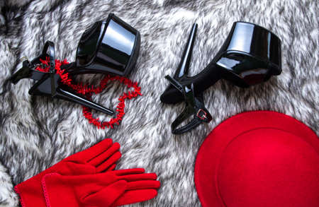 Flat lay collage with woman's black high-heeled shoes, red hat and gloves on wolf fur background. Female sandals with very high heels.