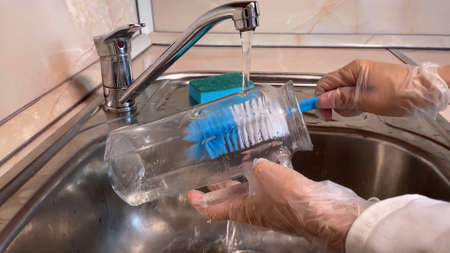 Woman washes glass jug in kitchen sink. Close up of pitcher, faucet and female hand in gloves. Water streaming. Brown background
