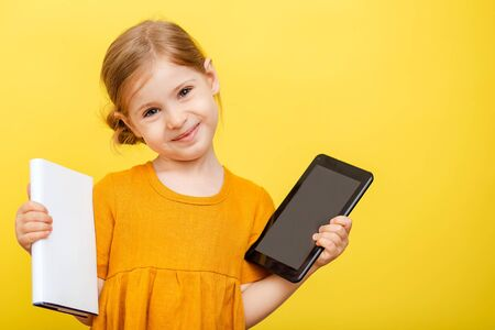 A little blonde girl in a yellow dress on a yellow background with a book and laptop. 免版税图像