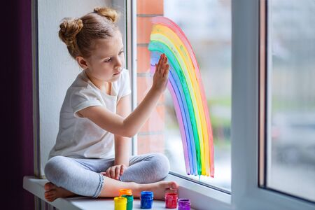 A little girl with blond hair is sitting in front of the window. The child is sad and looks out the window.
