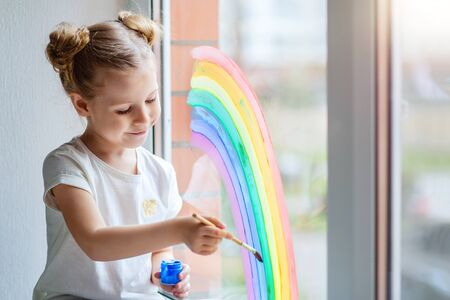 A little girl with blond hair draws a rainbow on the glass with paints.