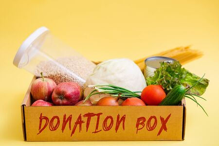 various food in a cardboard box and a donation sign on a yellow background, the concept of donation.
