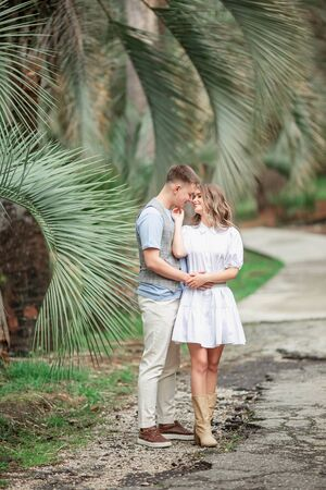 A happy couple in love walk in the Park under palm trees, holding hands. A guy and a girl in a relationship. Stock Photo