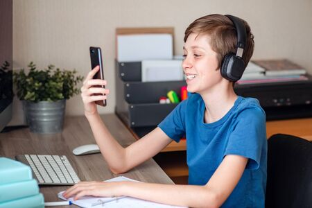 A teenage boy makes a video call using his mobile phone to his friends, classmates, and relatives. Joyfully shares the news Stock Photo