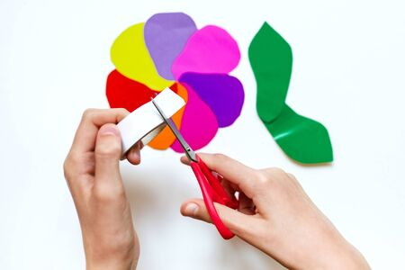How to make a flower at home from colored paper. Hands make a colorful flower out of paper, scissors and pencil. Step 4. Gather the petals into a flower. Project for children DIY art. Banque d'images