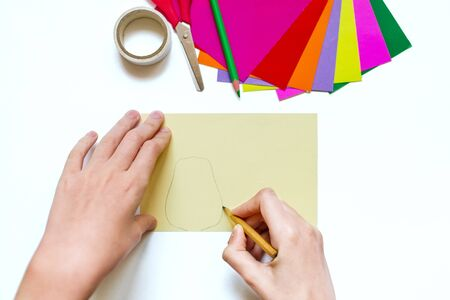 How to make a flower at home from colored paper. Hands make a colorful flower out of paper, scissors and pencil. Step 2. Draw a petal with a pencil. Project for children DIY art. Banque d'images