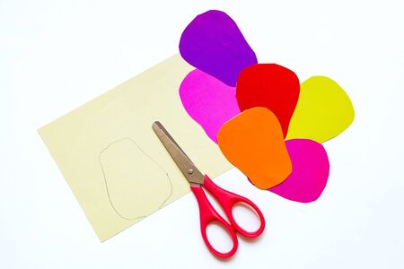 How to make a flower at home from colored paper. colorful flower out of paper, scissors and pencil. Step 3. With scissors cut out the petals. Project for children DIY art.