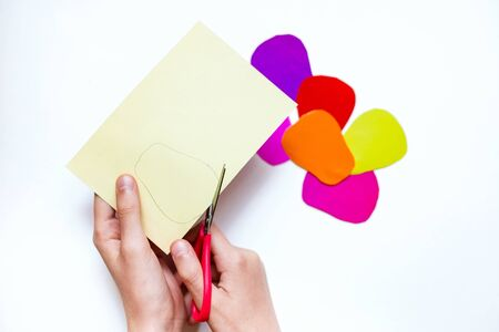 How to make a flower at home from colored paper. Hands make a colorful flower out of paper. Step 3. With scissors cut out the petals. Project for children DIY art. step by step instructions flower