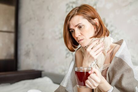 A sick young woman, sitting in bed with a scarf, suffers from a sore throat. Drinking hot tea. A woman with a fever wrapped in a blanket.