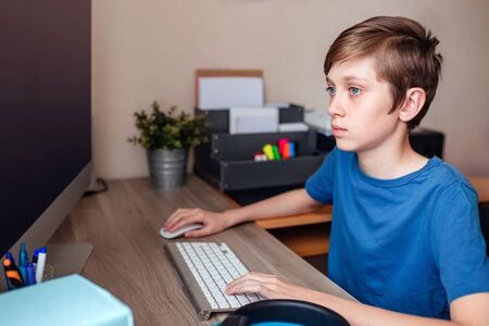 A teenage boy does homework, learns using a computer. Distance learning online. A child in quarantine in isolation learns independently at home. 版權商用圖片 - 146690878