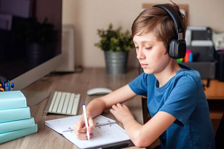 A teenage boy does homework, learns using a computer. Distance learning online. A child in quarantine in isolation learns independently at home.