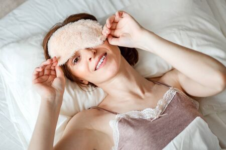 From above, a view of a healthy young woman laughing, removing her sleeping mask after a good nights rest is filmed. A happy red-haired lady feels energetic, full of energy in the early morning. Banque d'images