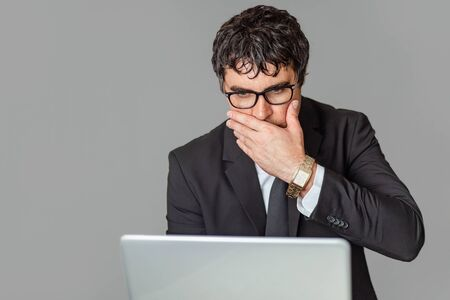 A male businessman in a black suit and glasses with a laptop. Bad news, disappointment. Grey isolated background.