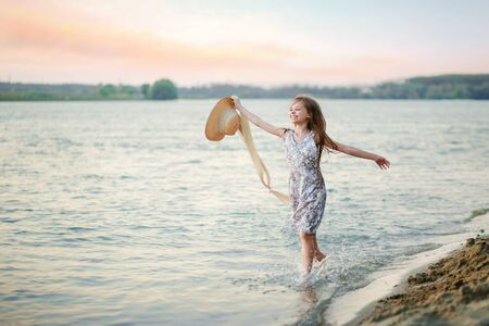 A happy young girl runs along the shore on the water and waves her hat. The girl is happy with the onset of summer
