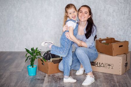 Cheerful mother little daughter is standing in a new apartment. A child has fun with an older sister a nanny or a loving mother active recreation and lifestyle concept. Stok Fotoğraf