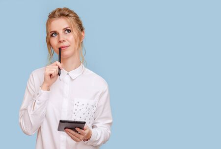 Portrait of an attractive young blonde woman with blue eyes working on a tablet. A young female entrepreneur freelance designer pondered the project, blue isolated background. Фото со стока
