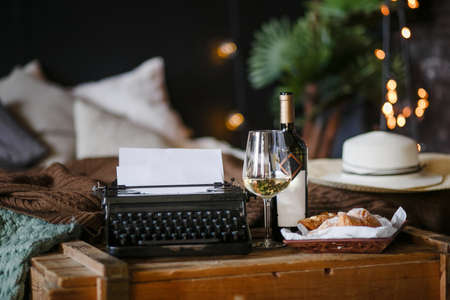 The inspiration of a writer typing texts on a vintage typewriter. Freelancer Breakfast croissants and wine. Office in the loft style