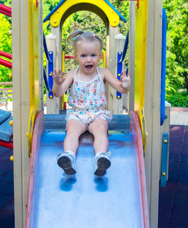 A little girl rides down a slide on a playground in the park. Holidays with children