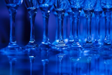Close-up of coupe glasses with reflections in blue light on blurred background