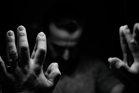 Der Mensch in der Verzweiflung mit erhobenen Händen und gesenktem Hand, monochromatisches Bild in einem niedrigen hellen Raum suchen vor dem Spiegel