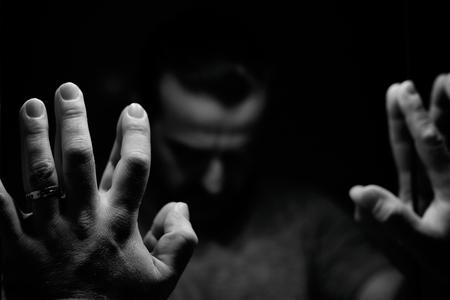 persona deprimida: Hombre en la desesperación con las manos levantadas y la mano inclinada, imagen monocromática en una habitación con poca luz que mira frente al espejo Foto de archivo