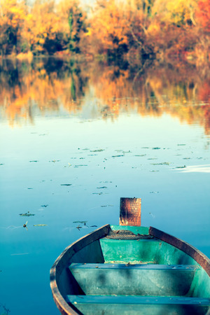 green boat: Old green boat on a blue lake, fall scene Stock Photo
