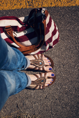 young girl feet: Women feet in summer flats with purple pedicure and with red and white stripped bag