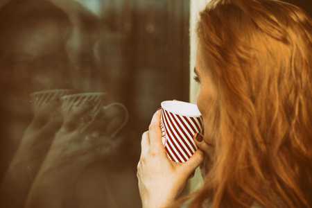 fresh girl: Woman looking through the window, drinking coffee, lost in thoughts