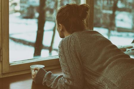손에 커피 잔으로 창문으로 슬픈 여자