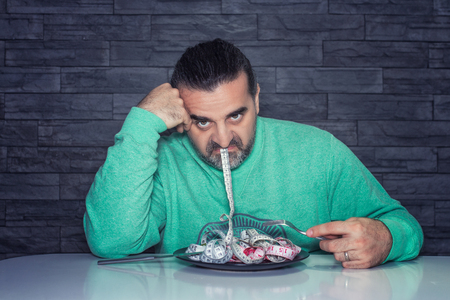 Man on diet, looking unhappy and disappointed, plate filled with measuring tape instead of food, diet and eating disorder concept Stock Photo