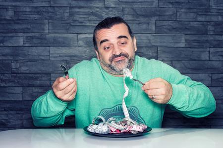 hombre comiendo: Hombre en la dieta, que parece infeliz y decepcionado, plato lleno de cinta métrica en lugar de los alimentos, la dieta y el concepto de trastorno de comer