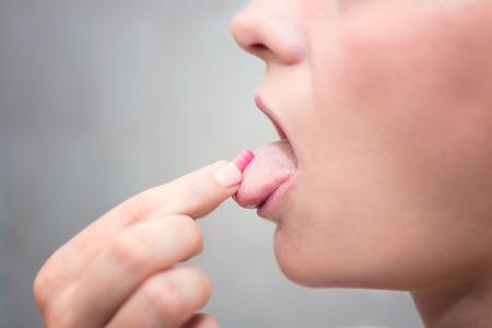 femme bouche ouverte: Femme prise de la pilule, bouche ouverte avec la langue sortie