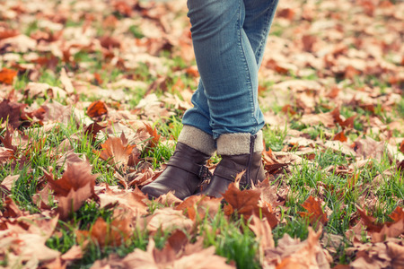 girl on a beautiful background: Woman legs in boots in the grass covered with autumn leaves