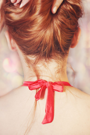Beautiful sensual woman with red hair and red bow around her neck, fingers in hair.