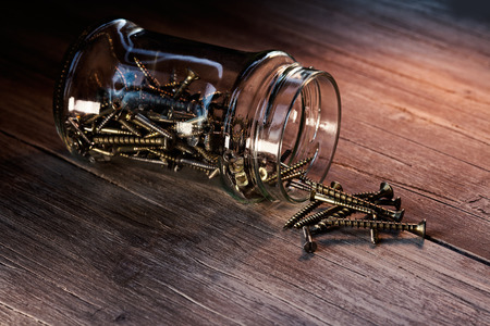 tornillos: Jarra llena de tornillos en una mesa de madera Foto de archivo