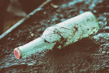 Old bottle with red cap laying in a dirt Stock Photo