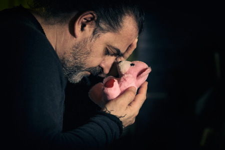pink teddy bear: Sad man holding pink teddy bear, concept of loss and mourning Stock Photo